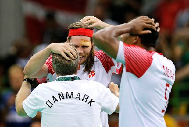 Landstræner Gudmundur Gudmundsson og Mikkel Hansen krammer med Mads Mensah Larsen som tilskuer. Foto: Jens Dresling/Polfoto